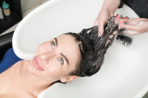 Professional hairstylist's hands wash long hair of brunette woman with shampoo in professional sink for shampooing in beauty salon.