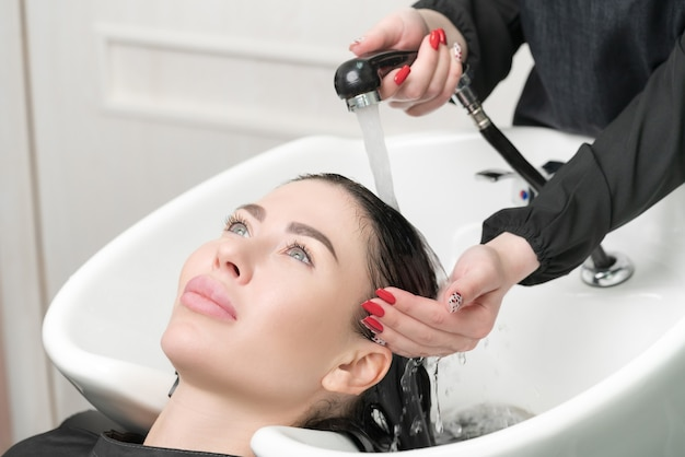 Professional hairstylist's hands wash long hair of brunette woman with shampoo in professional sink for shampooing in hair salon.