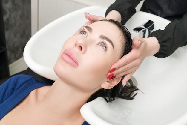 Professional hairstylist's hands wash long hair of brunette woman with shampoo in sink for shampooing in professional hair salon.