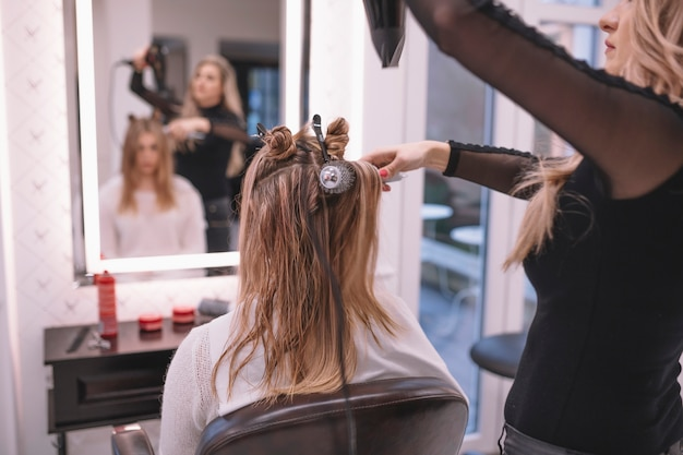 Professional hairstylist setting hair of client