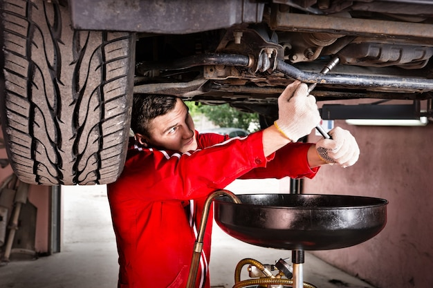 Professional handsome male car mechanic in uniform working underneath a lifted car