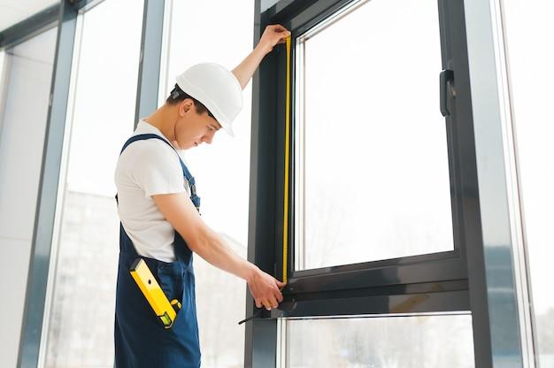 Профессиональный мастер, устанавливающий окна дома