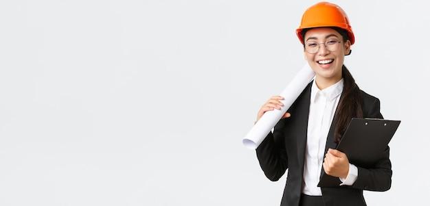 ヘルメットとビジネススーツを保持しているプロの幸せなアジアの女性建築家建設エンジニア...