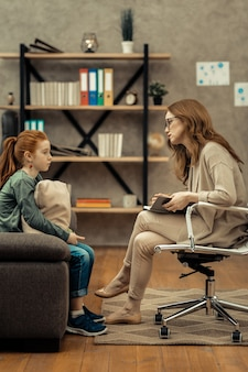 Professional help. professional female psychologist holding her notebook while listening to her young patient