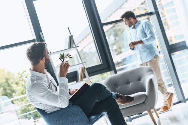 Professional help. young frustrated man looking away while having therapy session with psychologist