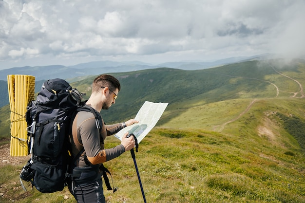 Professional hiker looking for the trail using paper map
