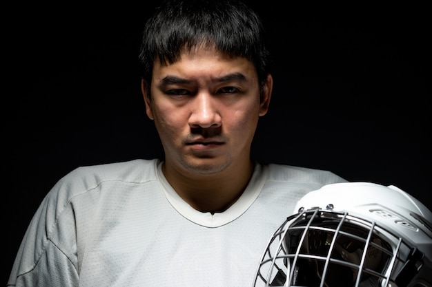 Professional ice hockey player feel angry, one lighting in dark room.