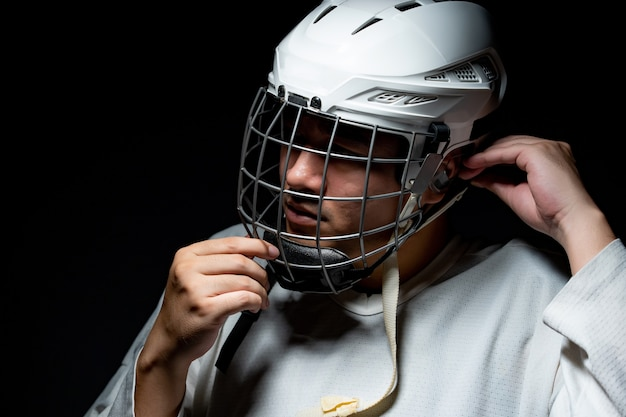Professional ice hockey player, one lighting in dark room.