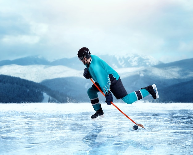 Professional ice hockey player in uniform exercise on frozen lake, winter forest on background. ice-skating outdoors