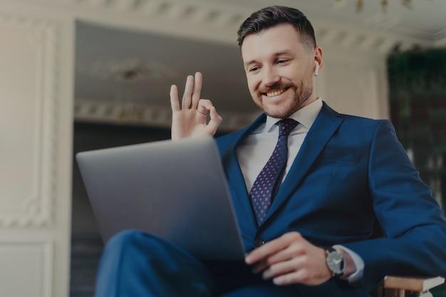 Профессионал в сфере бизнеса. счастливый успешный бизнесмен в синем темно-синем элегантном костюме показывает знак ок или жест хорошо, сидя в роскошном офисе и имея онлайн-видеозвонок на ноутбуке