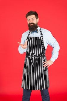 キッチンのプロ。あごひげを生やした流行に敏感なエプロンを調理する男。流行に敏感なシェフは赤い背景を調理します。あごひげを生やしたシェフの料理。流行に敏感な料理の家やレストラン。モダンなカフェのコンセプト。モダンな食事を作る。