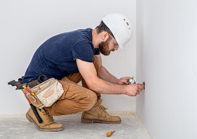 Профессионал в спецодежде с инструментом электрика на фоне белой стены. ремонт дома и концепция электромонтажа.