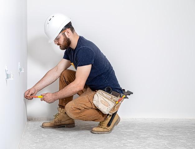 白い壁の背景に電気技師のツールを備えたオーバーオールのプロ。
