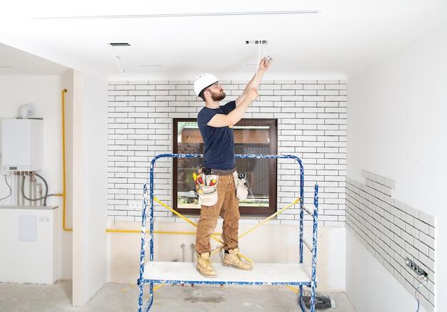 수리 사이트 전체 길이의 배경에 도구가있는 작업 바지 전문가. 홈 리노베이션 개념.