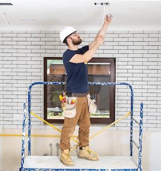Профессионал в спецодежде с инструментами на фоне ремонта в полный рост.