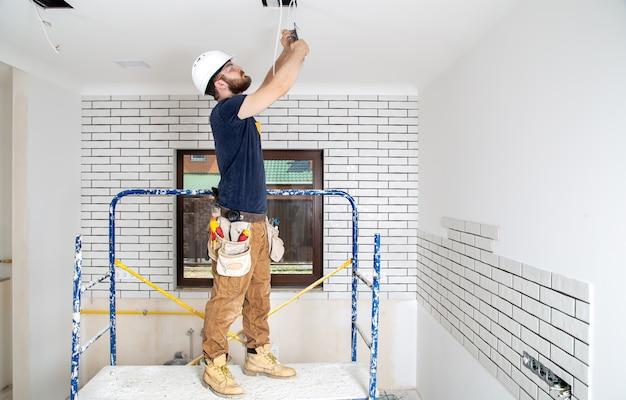 Профессионал в спецодежде с инструментами на фоне ремонтной площадки. концепция ремонта дома.