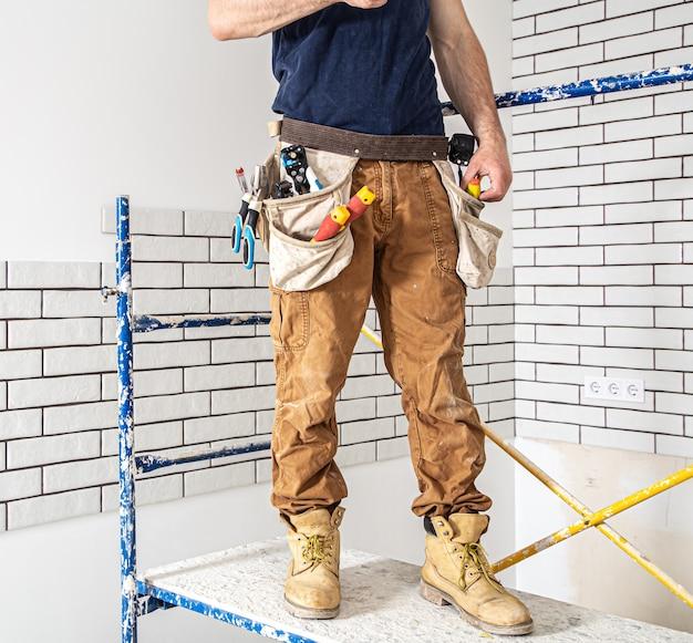 Профессионал в спецодежде с инструментами на фоне ремонтной площадки.