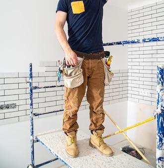 Профессионал в спецодежде с инструментами на ремонтной площадке.