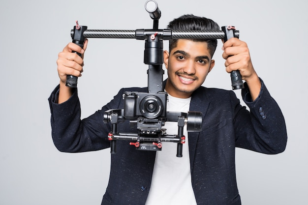 스튜디오 배경에 고립 된 gimball 비디오 slr ronin와 전문 인도 사람 동영상 제작자