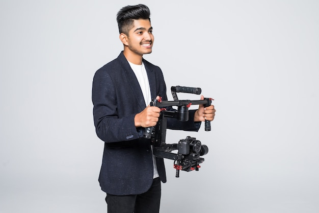 Профессиональный индийский мужчина видеооператор с видео gimball slr ronin, изолированных на фоне студии