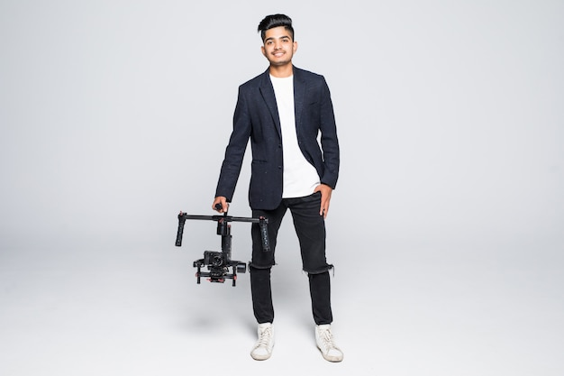 Professional indian man videographer with gimball video slr ronin isolated on studio background