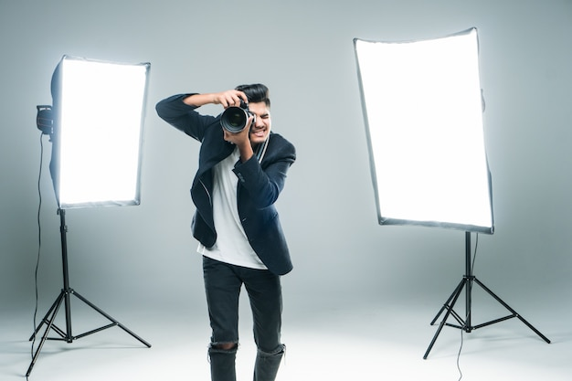 Professional indian young photographer taking photos in studio with leight