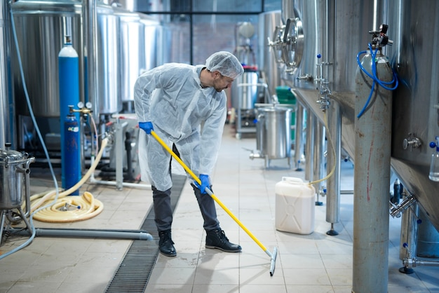 Professional industrial cleaner in protective uniform cleaning floor of food processing plant