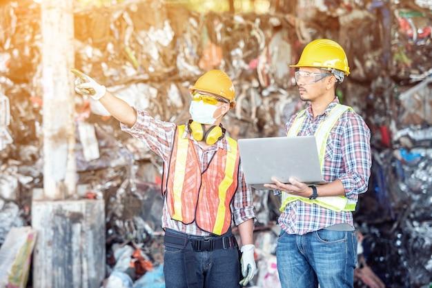 金属旋盤工業製造工場でラップトップコンピューターを使用している間、工場労働者とプロの産業機械エンジニア。