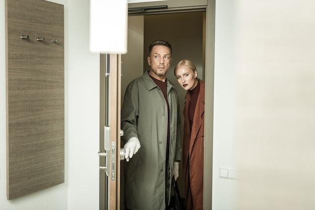 전문 검사관. 수사관으로 일하고 흥미롭게 유행하는 집을 조사하는 비옷을 입은 남녀