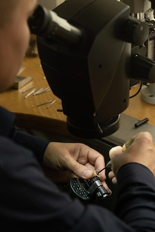 Профессиональный ювелир за работой. ювелир смотрит в микроскоп и украшает драгоценное кольцо красивыми камнями.