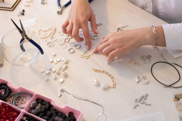 스튜디오 워크숍에서 수제 보석을 만드는 전문 보석 디자이너를 닫습니다. 패션, 창의성 및 수제 컨셉