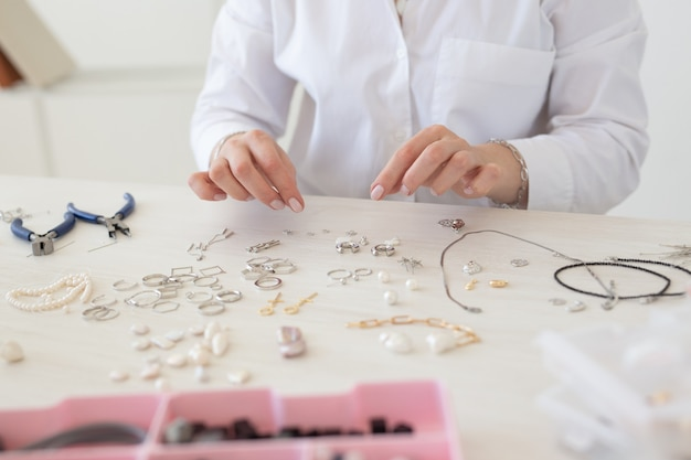 스튜디오 워크샵에서 수제 보석을 만드는 전문 보석 디자이너가 가까이 있습니다. 패션, 창의성 및 수제 개념