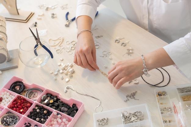스튜디오 워크샵에서 수제 보석을 만드는 전문 보석 디자이너는 패션 창의성을 닫습니다