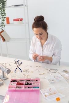 Профессиональный дизайнер ювелирных изделий, изготавливающий украшения ручной работы в мастерской студии модного творчества и