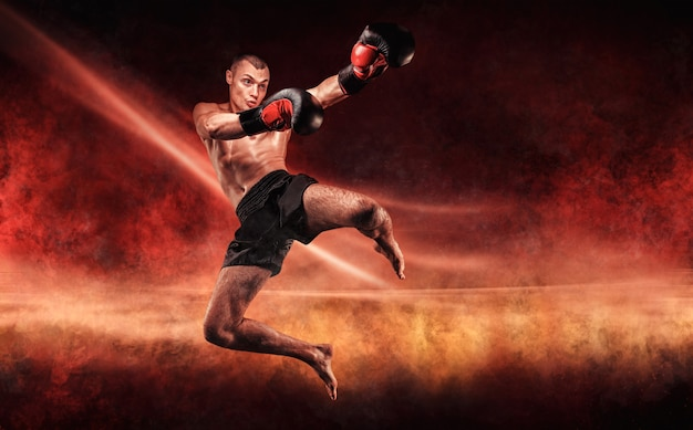 Профессиональный кикбоксер прыгает с вытянутым коленом. огненная арена. смешанные боевые искусства. спортивная концепция.