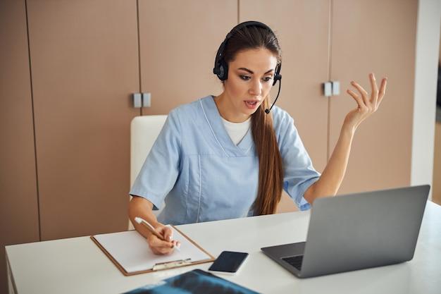 彼女のラップトップに取り組んでいる医療制服のプロの女性