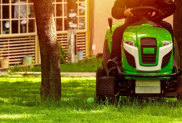 Профессиональная газонокосилка косит зеленую лужайку в парке.