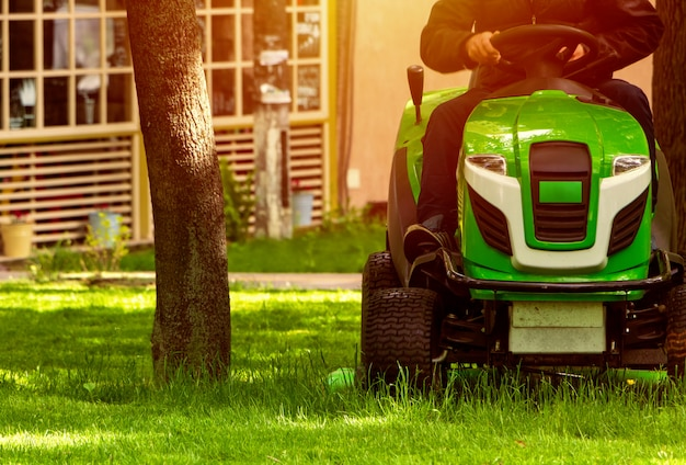 Professional lawn mower mows a green lawn in a park.