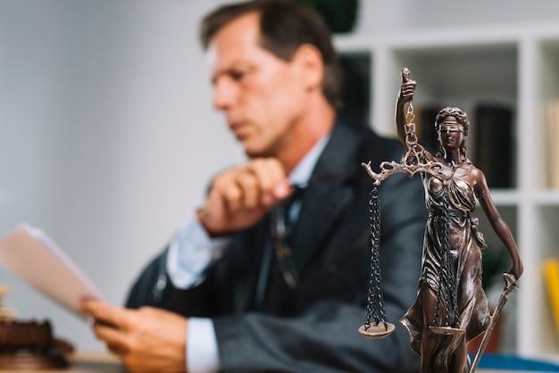 Профессиональный адвокат, читающий документ с статуей правосудия на переднем крае