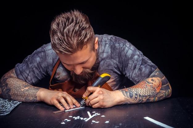 Профессиональный кожевник, вырезающий контуры кожи для своей новой продукции в кожевенной студии