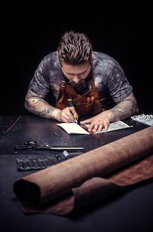 Профессиональный кожевник вырезает контуры кожи для своей новой продукции на рабочем месте.
