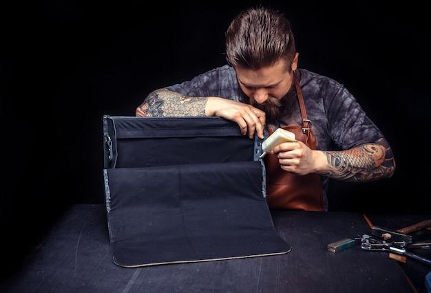 책상에서 새로운 제품 조각에 가죽 작업을 수행하는 전문 가죽 노동자
