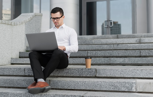 Professional looking on laptop outdoors