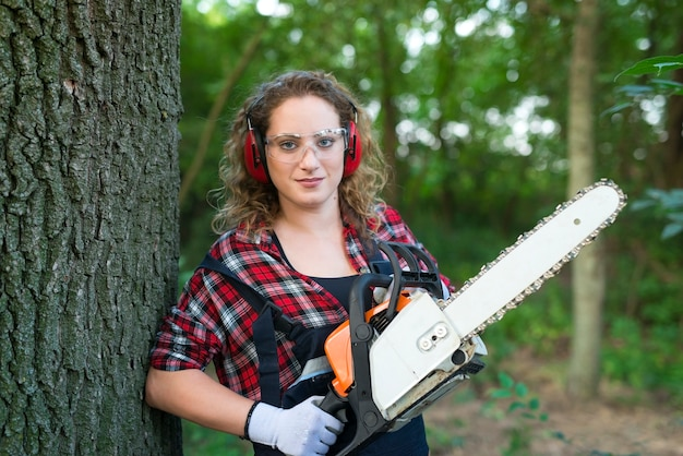 Professional lumberjack in the forest cutting an oak trunk with chainsaw