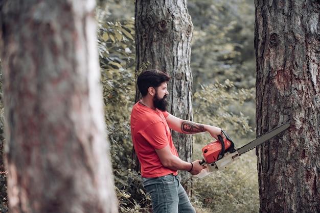 Профессиональный дровосек, держащий бензопилу в лесу, дровосек с топором или бензопилой летом ...
