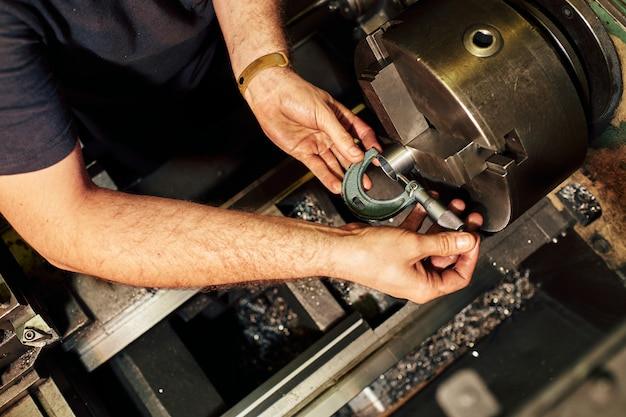 Professional machinist : man operating lathe grinding machine