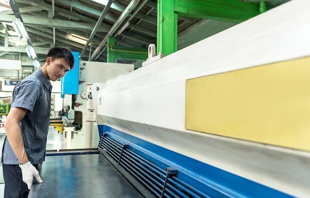 Professional machinist operating industrial shearing machine