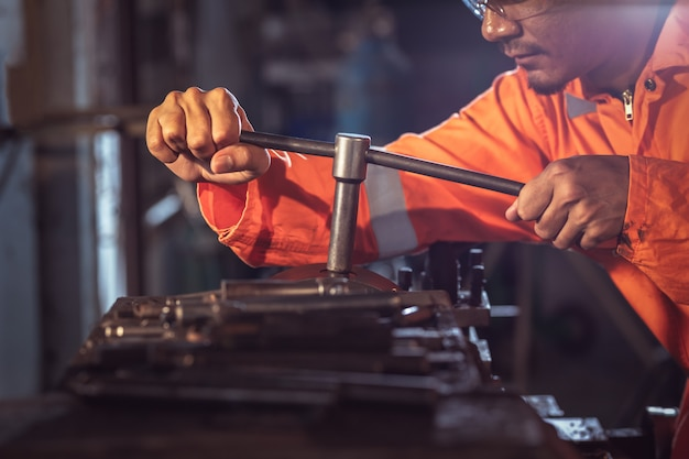 Professional machinist : worker handles metal at lathe operating lathe grinding machine in uniform with safety