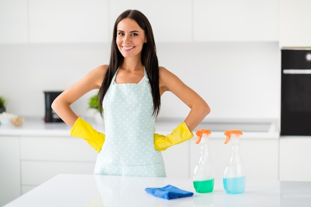 プロのメイドのコンセプト、キッチンハウスのアパートで効果的なスプレー洗剤仕上げの雑用を持っている黄色のラテックス手袋を着用しているポジティブな主婦の肖像画