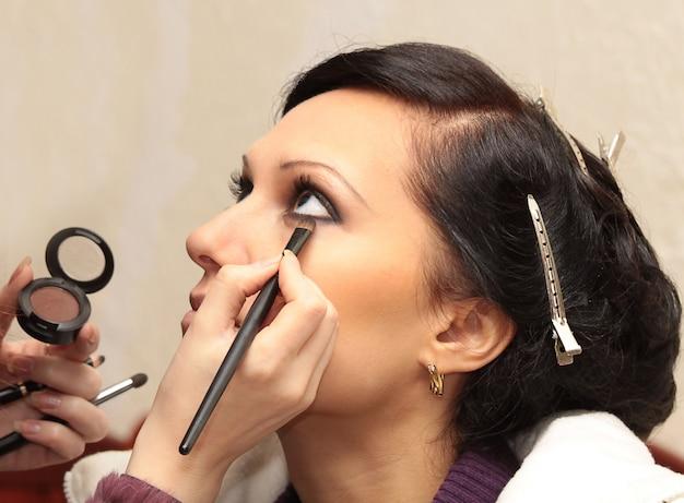 Профессиональный визажист, наносящий макияж на подростковой модели